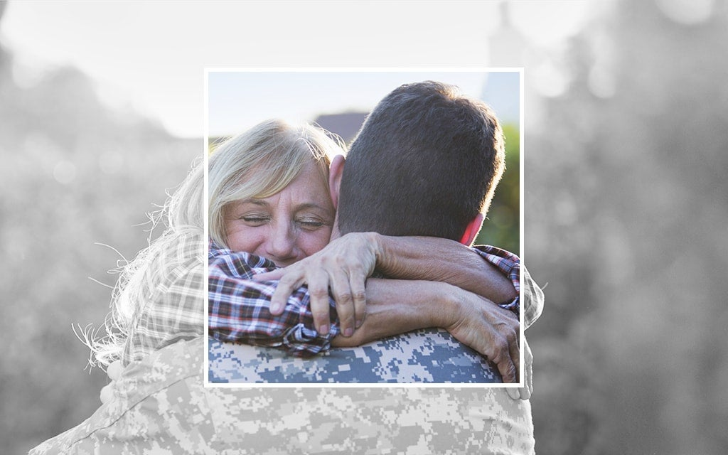 Greyed out image with coloured box and military family hugging inside
