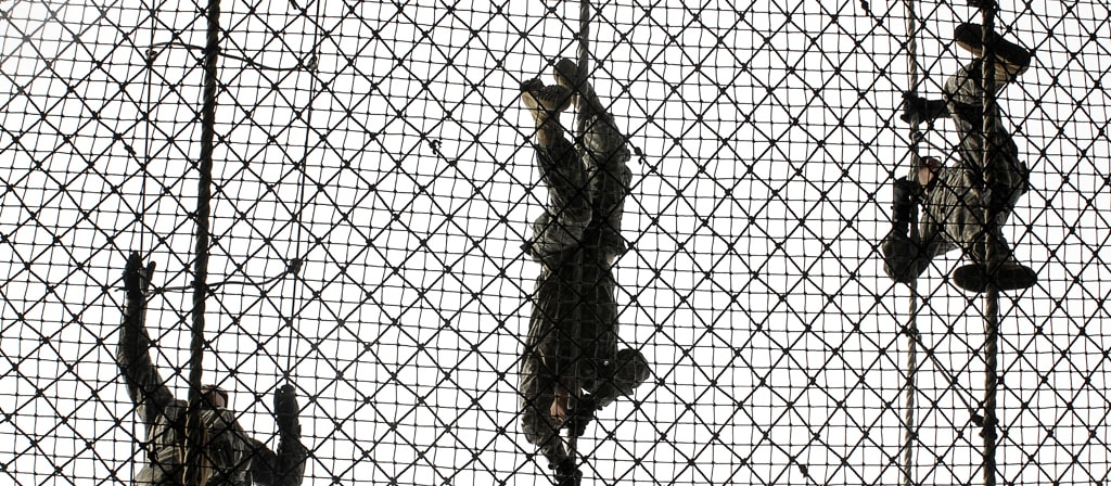 A group of soldiers climbing ropes in an obstacle course.