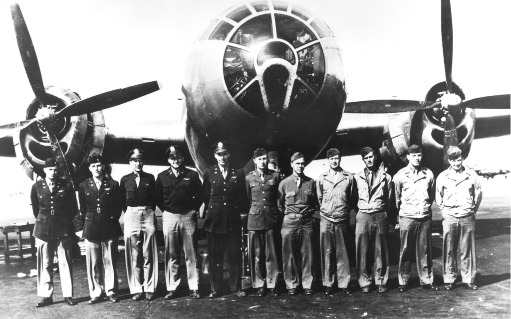 A black and white photo of a group of uniformed US military officers standing in front of a World War II bomber.