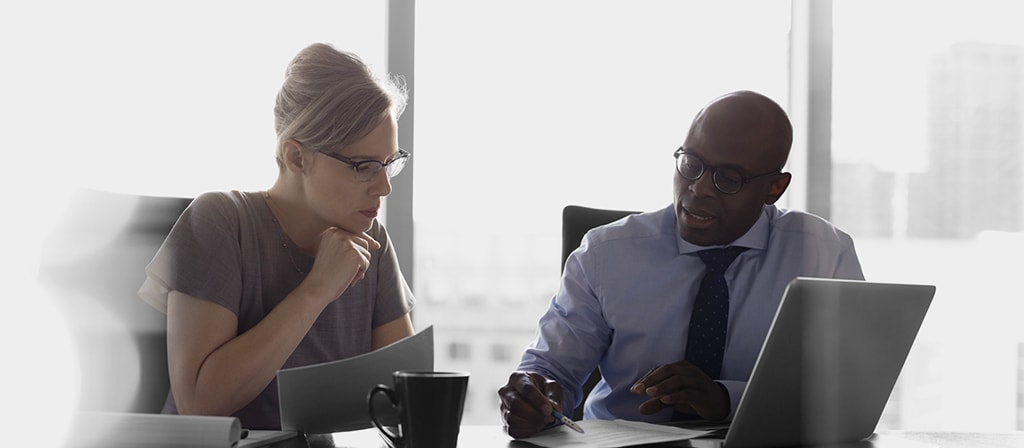 A male financial advisor sitting down with a young woman in an office and discussing her asset management strategy.