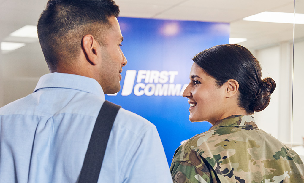 A civilian man and a female solider in uniform walking into a First Command branch.